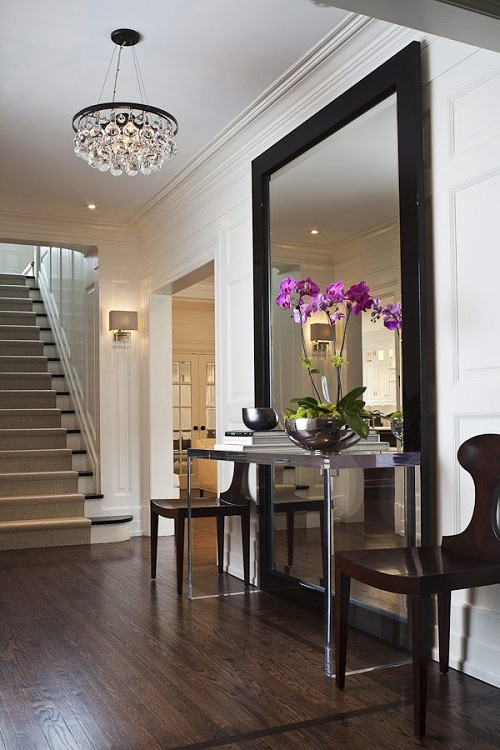Framed mirror in entry with transparent table
